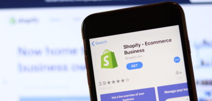 Phone with Shopify icon on screen close up with blur website on laptop. Los Angeles, California, USA - 30 November 2019, Illustrative Editorial